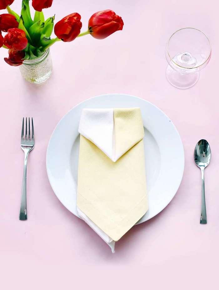 table mariage avec assiette blanche et idée intéressante de pliage de serviette en papier deux couleurs, deco en bouquet de tulipes rouges
