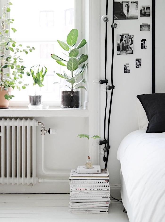 deco chambre noir et blanc avec des touches vertes apportés par des pots de plantes rangés sur le rebord fenêtre, murs blancs, linge de lit noir et blanc, photos noir et blanc, piles de magazines et livres sur parquet blanchi
