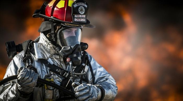 un jeune pompier dans son uniforme couleur d'argent, casque rouge et jaune, masque de protection