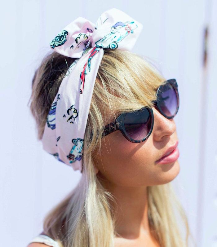 foulard cheveux rose imprimé fantaisie attaché avec noeud au dessus comme pin up sur femme blonde avec lunettes de soleil