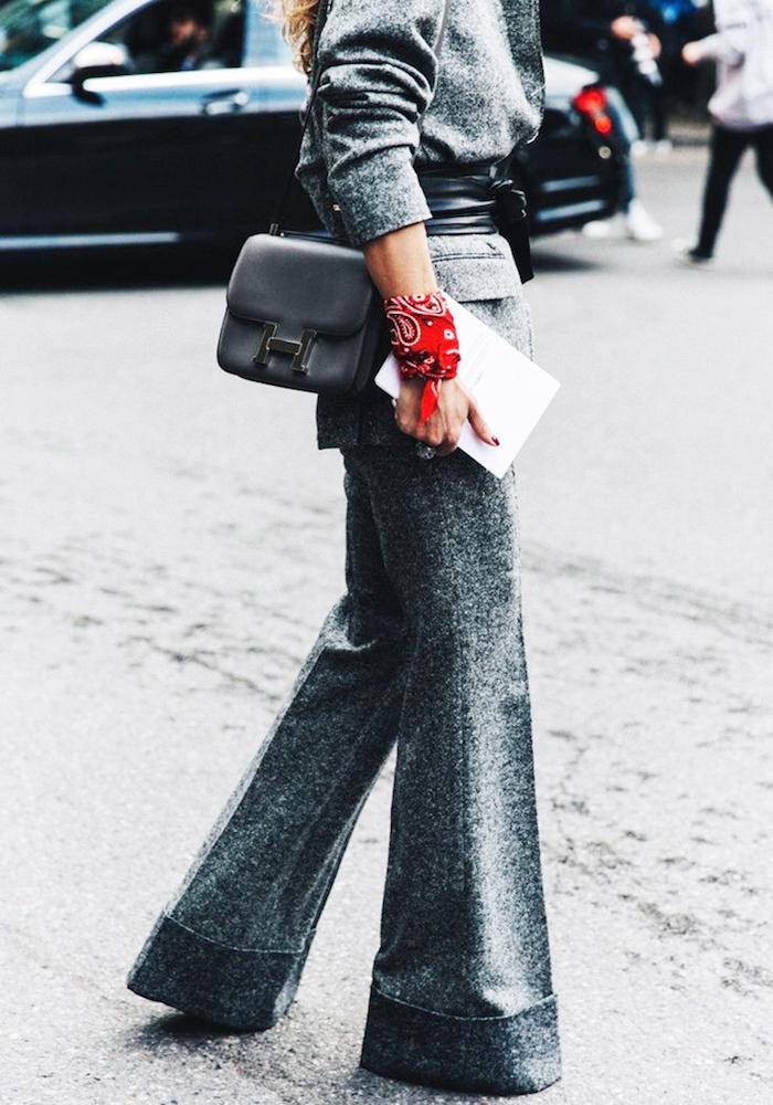 femme avec tailleur patte d ef gris chiné et bandana rouge attaché au poignet comme un bracelet mode boheme chic