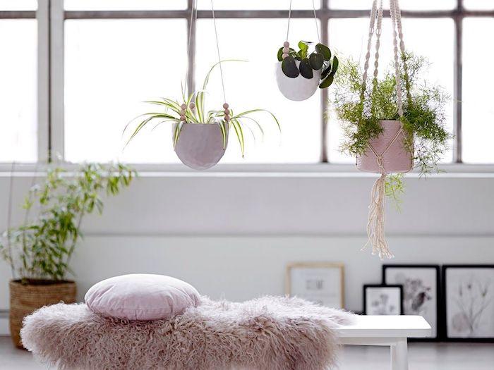 pots suspendus au dessus d un banc blanc, décoré de plaid et coussin décoratif rose, murs blancs, tableaux d art