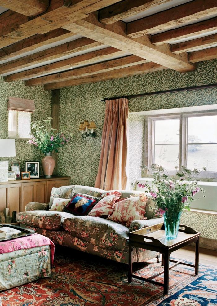 déco maison de campagne, sofas floraux, ottoman au tapissier rustique, poutres en bois, rideau rose, vase en verre avec fleurs des champs