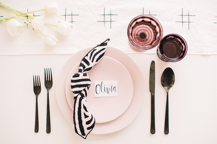 comment décorer une table de mariage de manière originale, assiettes rose, marque plage en lettres, couverts argent, serviette en noeud motif zèbre