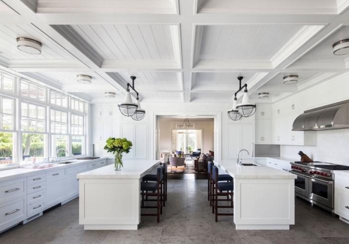 agencement de cuisine spacieuse avec deux îlots, modèle de cuisine blanche avec accents en inox et noir mate