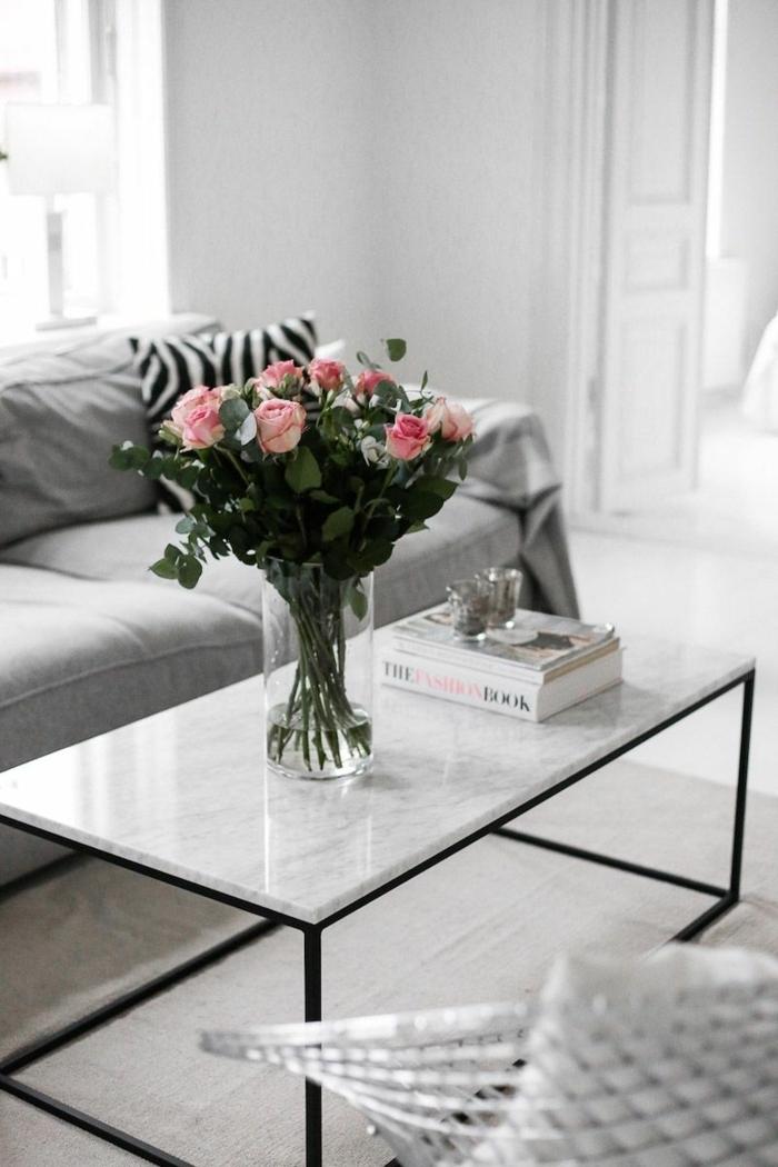 table basse marbre et fer, vase avec roses, livres blancs, sofa gris, intérieur gris clair, petits bougeoirs