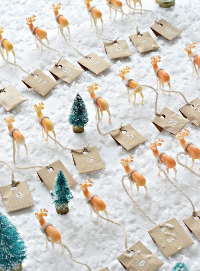 calendrier de l avent en petites figurines de cerfs, rennes de noel avec de petits sachets kraft accrochés, figurines de sapins sur neige artificielle