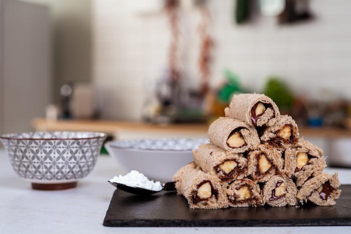faire des roulés à partir de tranche de pain de mie tartinée de chocolat avec baton de banane à l interieur, recette pain perdu