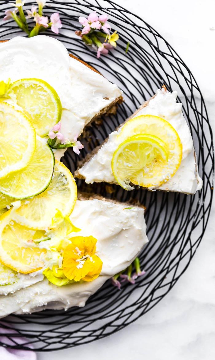 gateau sans lait paleo et vegan au citron, avec un glaçage de chantilly végétalienne à la noix de coco, décoré de tranches de citron et de fleurs comestibles
