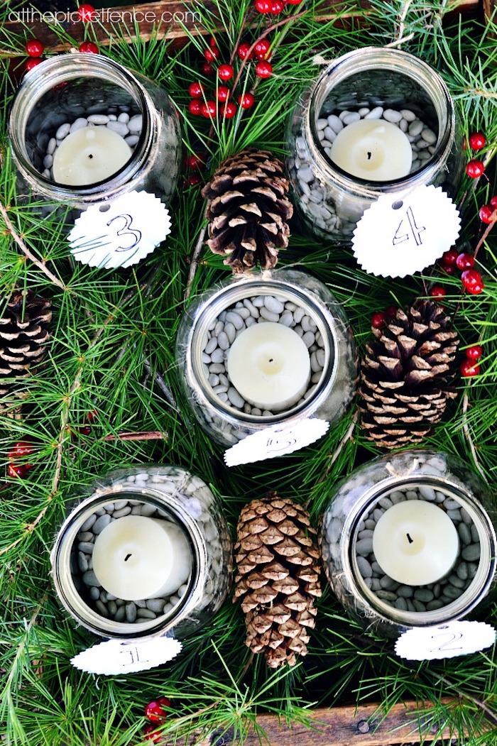 idée de bocal en verre rempli dе haricots blancs avec une bougie blanche à l intérieur, branches de pin, houx et pommes de pin décoratives