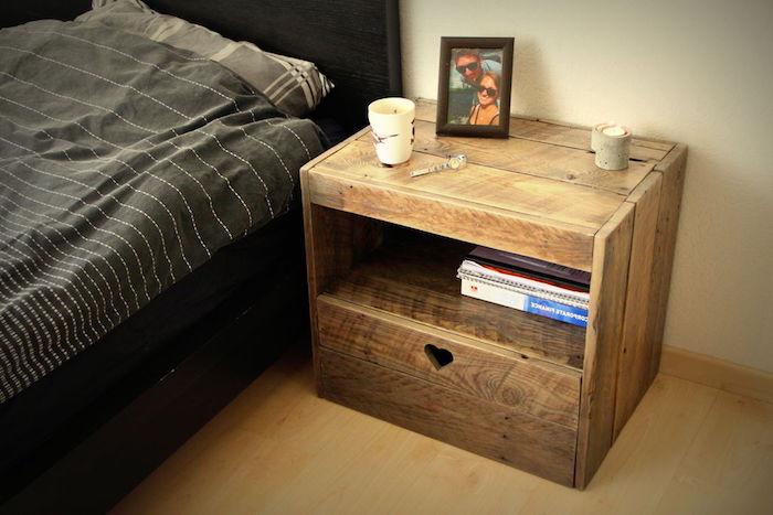 table de chevet en palette, planches de bois décomposées avec rangement pour vos livres de chevet, cadre photo près d un lit décoré de linge de lit gris