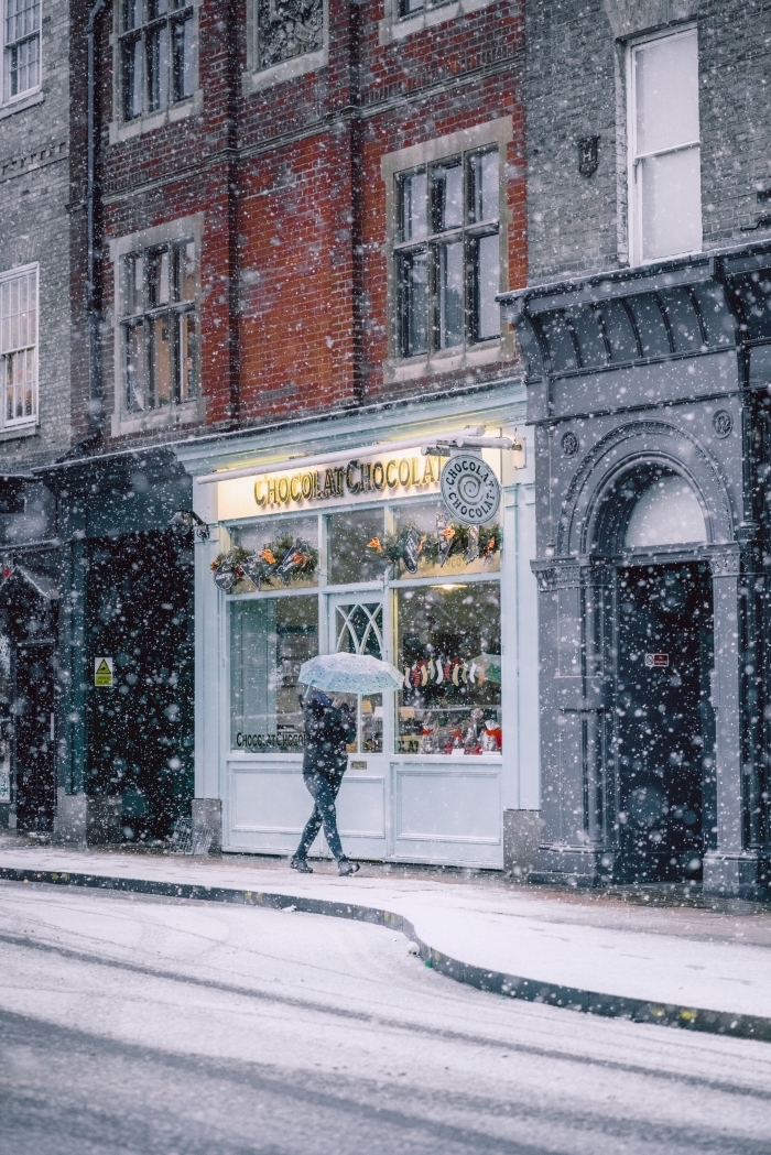exemple paysage d'hiver pour fond d'écran verrouillage iphone, photo hiver et flocons de neige devant la vitrine d'un magasin décoré pour noel