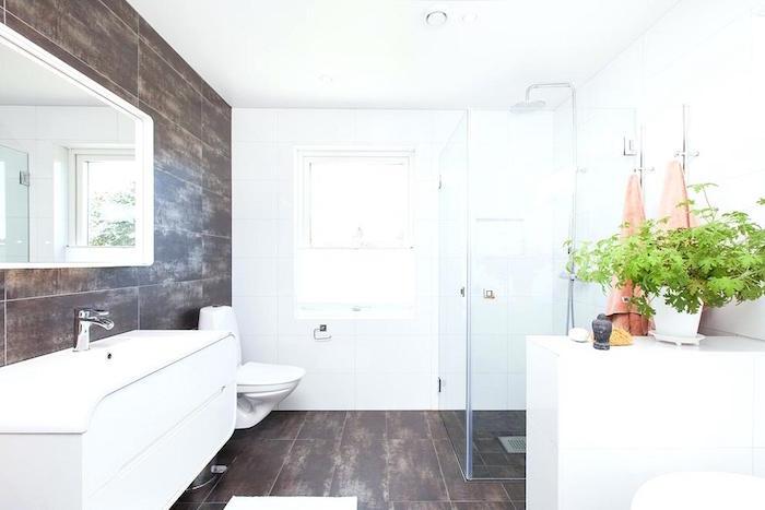 salle de bain ouverte avec coin douche italienne avec carrelage mur et sol marron et murs blancs avec déco plante verte