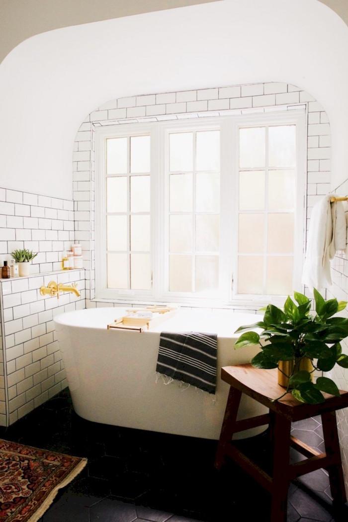 baignoire ilot blanche profonde dans salle de bain avec grande fenetre et mur en carrelage blanc norvegien