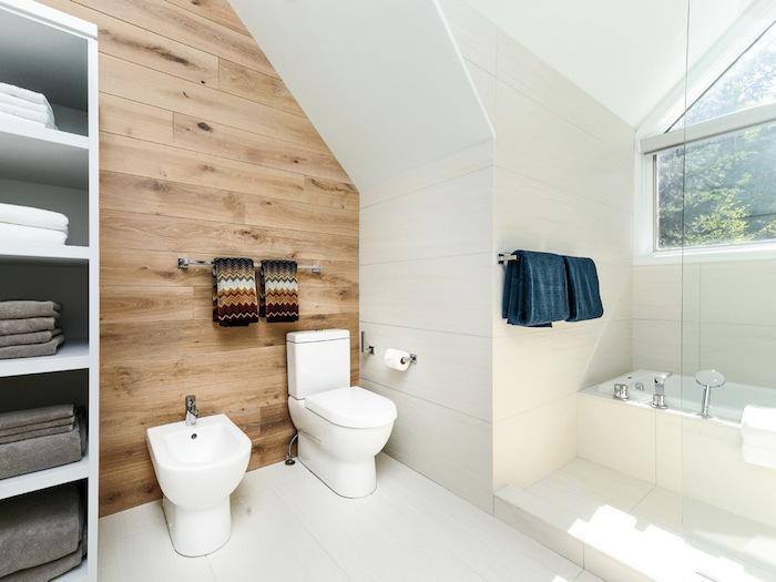salle de bain scandinave avec mur en bois de parquet et carrelage blanc sur le sol et les murs