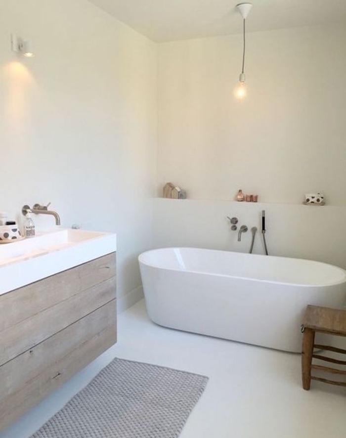déco de salle de bain minimaliste type scandinave avec murs blancs et baignoire blanche ovale et meuble en bois avec grande vasque rectangle