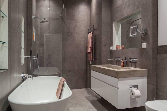 petite sdb gris couverte de carrelage sur les murs et sol en béton ciré avec douche à l italienne et lavabo en ciment type scandinave