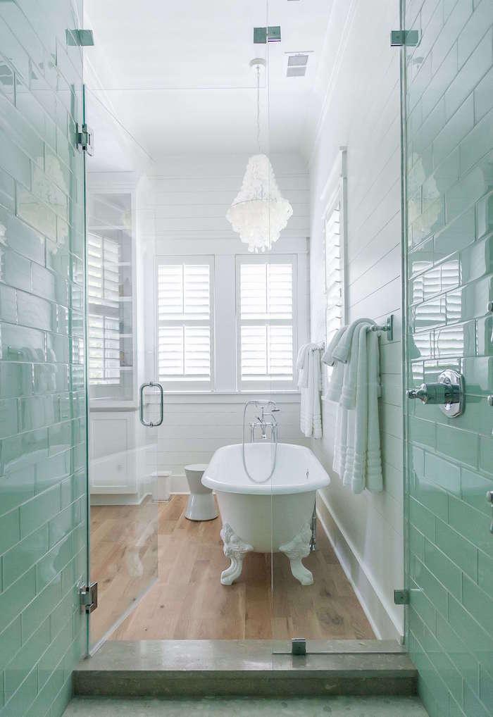 modele de salle de bain ambiance rétro avec baignoire vintage sur sol en parquet bois et murs blancs style scandinave et chandelier de sdb