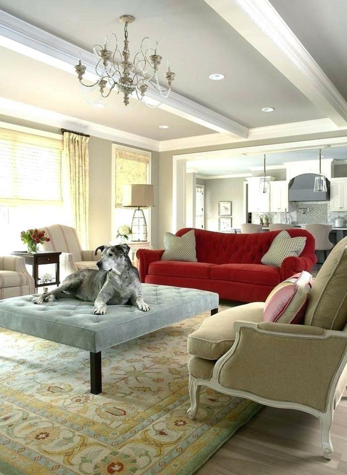 tapis persan, chandelier épuré, sofa rouge, grand ottoman gris clair et chien gris, salon cosy déco campagne esprit brocante