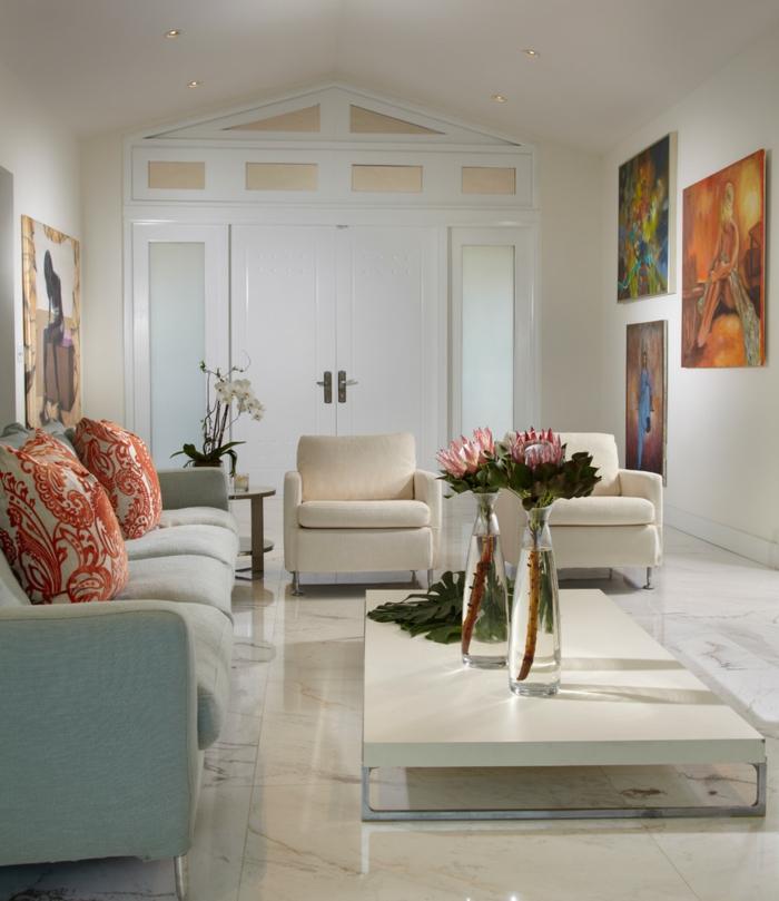 salle de séjour blanche, sofa gris clair, coussins aux motifs floraux, deux vases de verre avec des fleurs, tableaux peintures