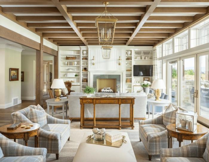 grand salon aux poutres apparentes, fauteuils carrés, table ronde en bois, ottoman clair, grande lanterne suspendue, étagères murales