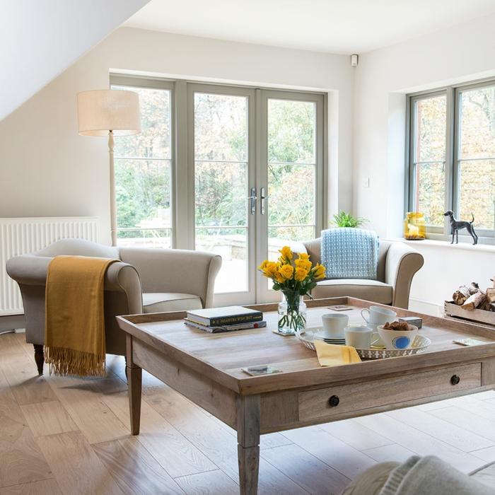 fauteuil gris, plaid moutarde, table basse bois, vase en verre avec roses jaunes, fenêtres grises, plateau avec tasses
