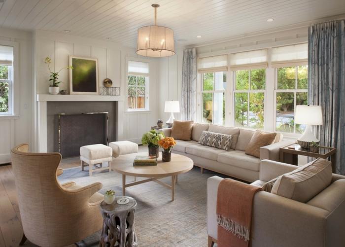 salon équipé avec tapis couleur gris clair, fauteuil crème, table ronde en bois clair, plafond lattes blanches
