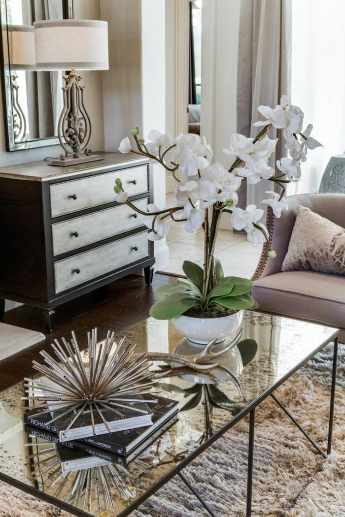 table basse en verre, grande orchidée blanche, lampe de table abat jour sur une commode vintage, tapis poilu beige