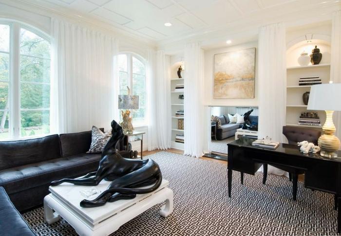salle de séjour, table basse blanche, sculpture de chien noire, sofas noirs, porte-fenêtres, grand bureau noir