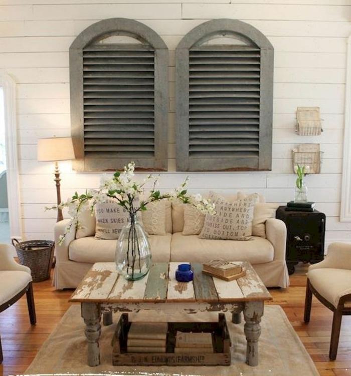 salon en beige et blanc, table basse shabby, tapis beige clair, sofa beige, coussins de jute, lambris mural en bois