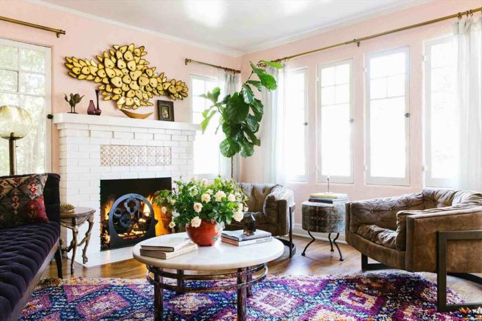 tapis aux couleurs pétillantes, table ronde, cheminée blanche, vase avec roses, peinture mur rose, sofa capitonné, sofa en cuir