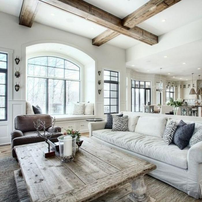 déco style campagne chic, table en bois brut, poutres apparentes, sofa gris clair, tapis en jute, alcove sous la fenetre, banquette