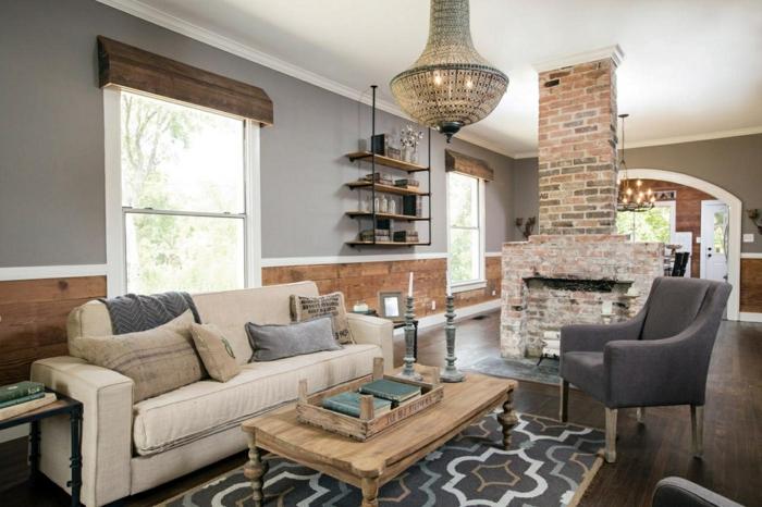 table de salon en bois, chandelier suspendu, cheminée en briques, mur gris, étagère murale, grand salon cosy