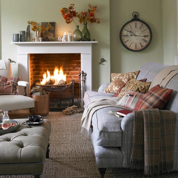 sofa gris, ottoman capitonné, cheminée murale déco briques rouges, grande horloge ancienne, coussins à carreaux, tapis en jute