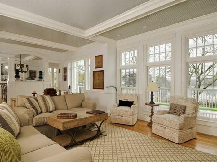 grand salon lumineux, tapis beige géométrique, table en bois brut et fer, portes-fenêtres, sofas couleur taupe