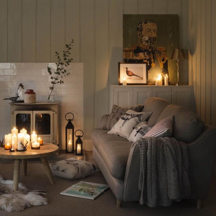 déco cocooning salon vintage aux murs revêtus de lambris blanc, une multitude de bougies parsemés un peu partout du salon