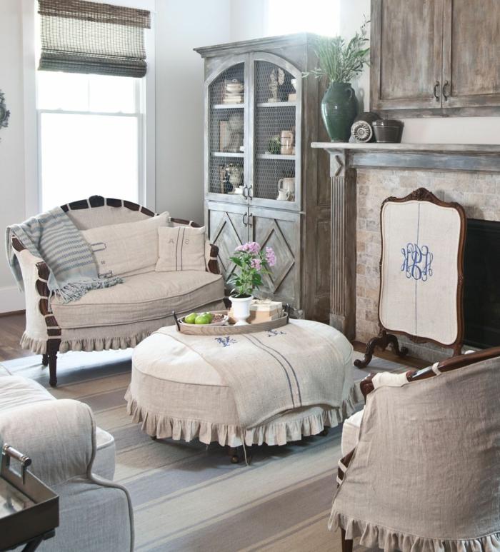 table ottoman couverte de lin, plateau rond, meuble esprit brocante, cheminée, placard bois vieilli, vaisselier