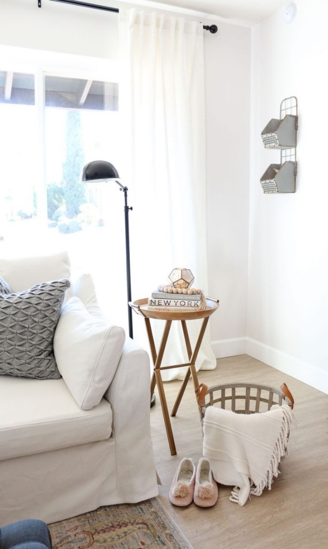 coin de détente dans un salon blanc de style scandinave avec un canapé blanc décoré d'un coussin gris à motifs texturés, une table d'appointe au design vintage et un panier de rangement