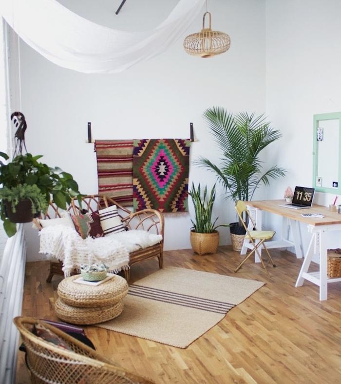 deco boheme chic salon moderne avec coin bureau, fauteuil rotin avec plaid blanc, parquet clair, plantes vertes et tapis deco murale