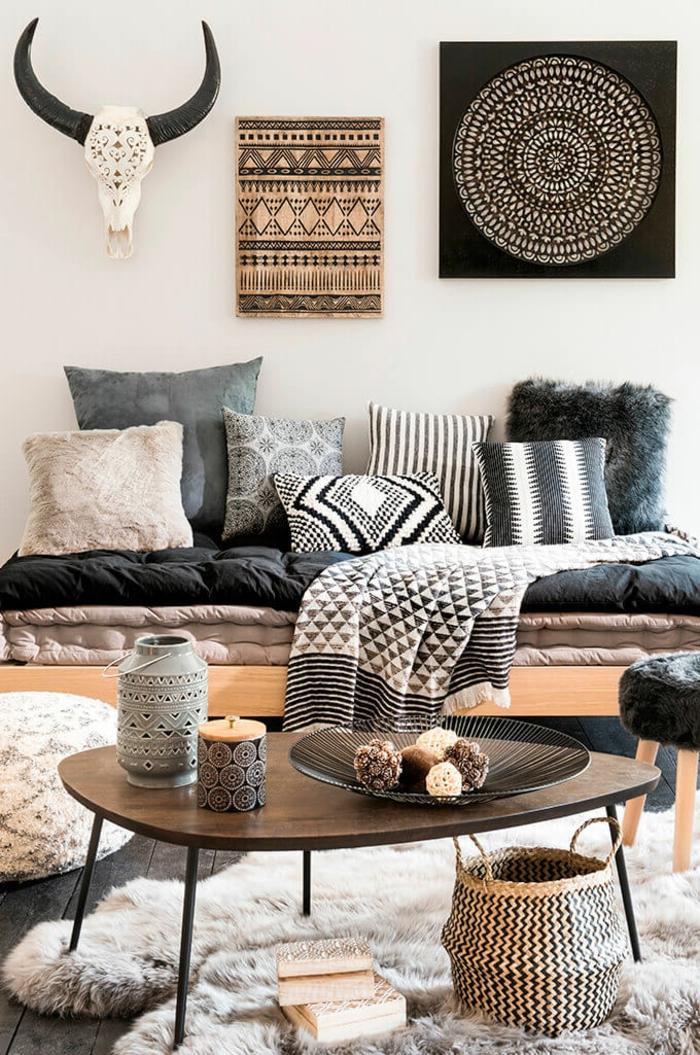 table basse en bois, bougie et lanterne, grande assiette aux objets décoratifs, coussins en gris et blanc, tentures murales, tapis fourrure
