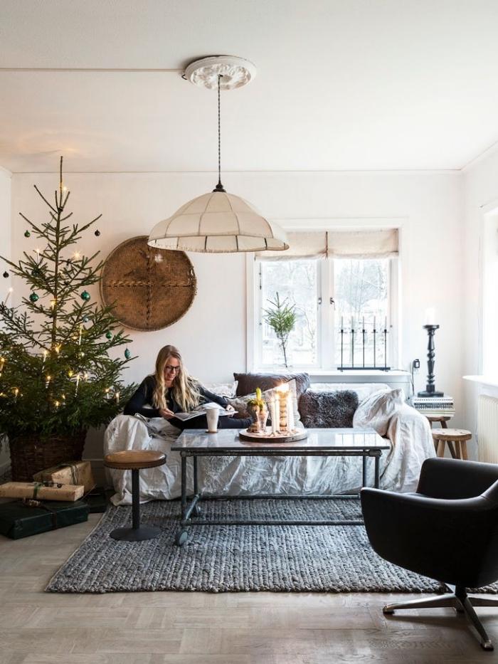 deco sejour d'esprit de fête scandinave et traditionnelle, un coin de détente dans le salon avec un petit canapé accessoirisé de coussins gris en fausse fourrure et un sapin de noël posé à son côté
