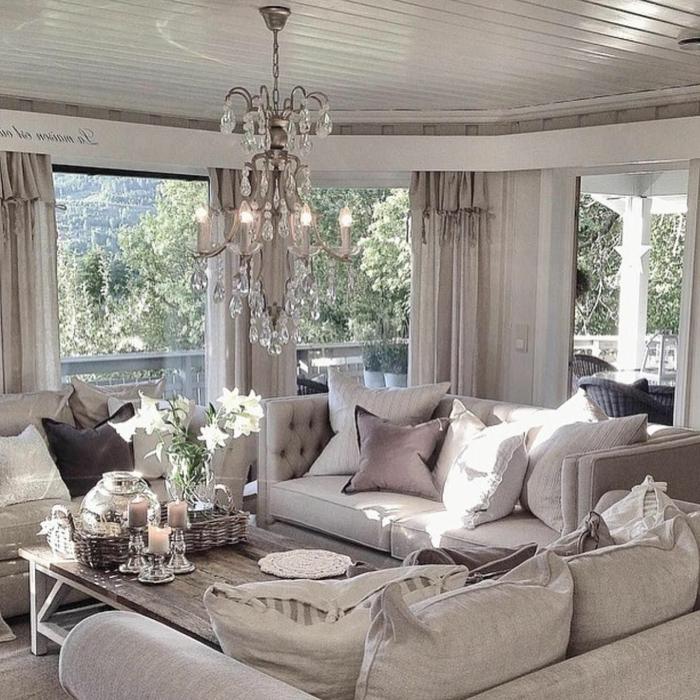 sofas gris clair, table basse en bois, bougeoirs argentés, grand plafonnier cristal, coussins beiges et taupe