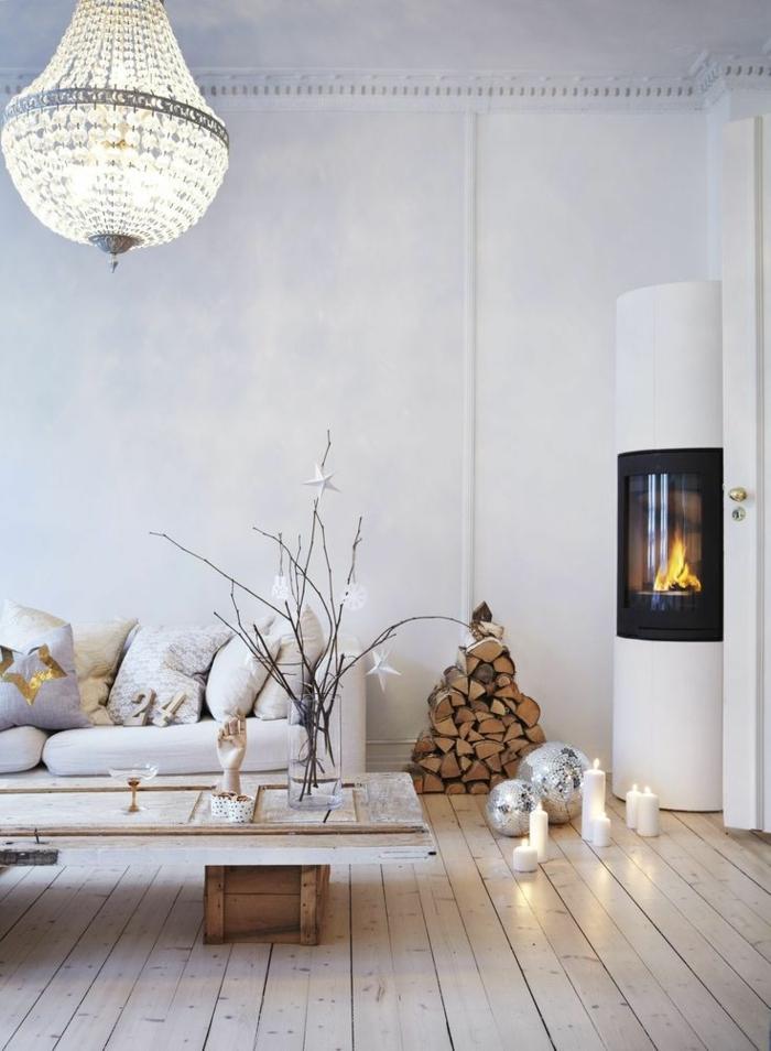plafonnier en cristal oriental, poêle scandinave, range-bûches, bougies allumées, table rectangulaire, bougies blanches