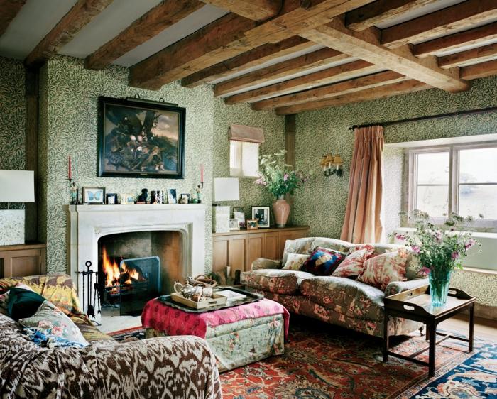 salon motifs colorés, ottoman, cheminée, papier peint vert, plafond en poutres, sofa shabby bariolé, tapis persan, cheminée