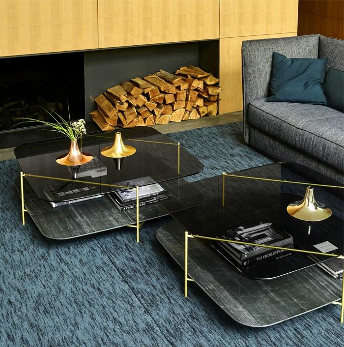 deux tables au piétement doré et plateau de verre, tapis bleu, sofa gris, range-bûches, coussin couleur pétrole