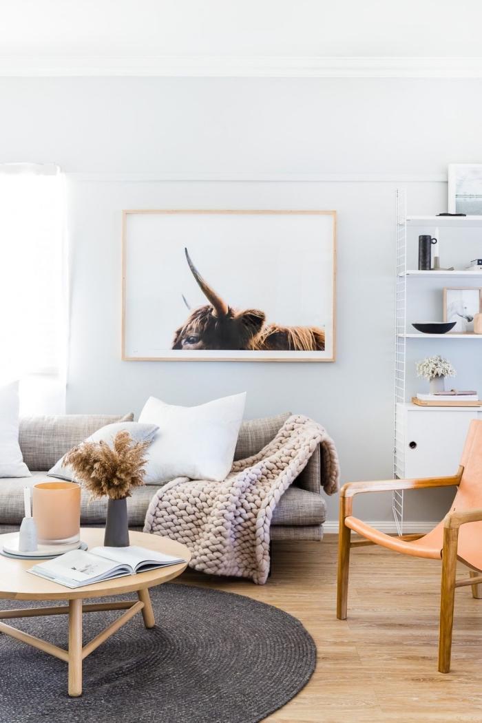 deco cocooning dans un salon de style scandinave vintage en tons neutres, canapé beige avec plaid grosse maille enveloppante, surmonté d'un cadre photo aux couleurs harmonisant avec le décor