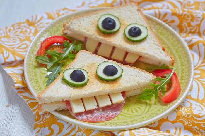 sandwich triangulair avec toast grillé motif monstre, bouche et dents en saucisson, fromage et des yeux en concombre et olive