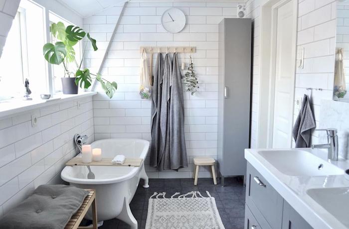 aménager une petite salle de bain mansardée avec murs en carrelage blanc et sol gris avec meuble double vasque et baignoire ilot retro scandinave