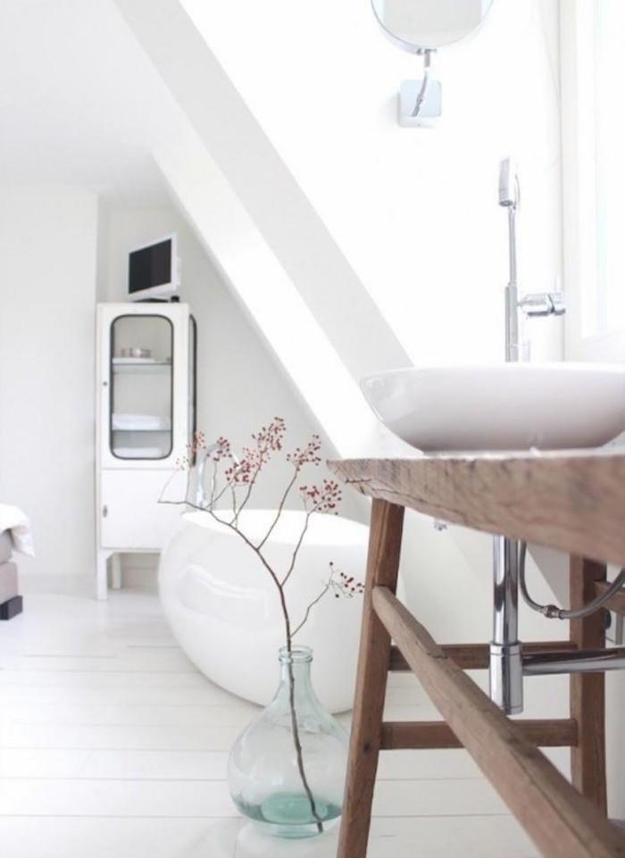 photo sdb aménagée sous les combles avec déco scandinave blanche rétro moderne cosy avec murs blancs baignoire et vasque brillant design et meuble lavabo en bois rustique vintage sur parquet blanc