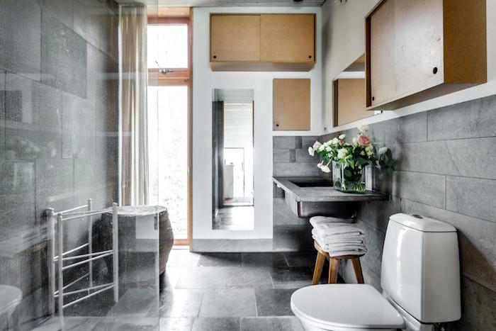 salle de bain rétro avec meuble et déco vintage en bois à la scandinave et carrelage gris sur sol et murs et lavabo en béton ciré